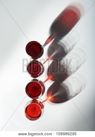 shadows from red wine glasses on white background view from top