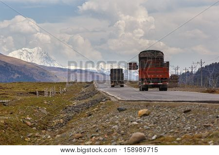 Truck on the road in Tibet under snow mountain Sichuan China