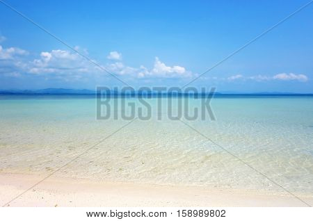 White clouds on blue sky over calm sea. Clear blue sky with fantastic white sand beach with calm ocean Summer outdoor nature holiday serenity. Talu Island Prachuap Khiri Khan Thailand.