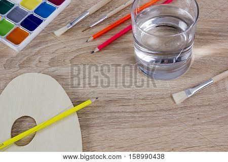 Variety of tools of the artist on the table with a wooden surface