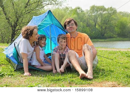 Happy family - mother, father, little girl and boy - sitting in blue tent and laughing on green lawn on bank of river at sunny day