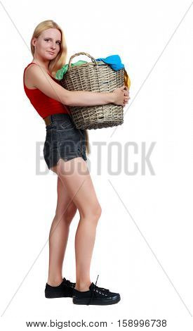 Back view of woman with  basket of dirty laundry. girl is engaged in washing. Rear view people collection.  Isolated over white background. Long-haired blonde in shorts holding a laundry basket.