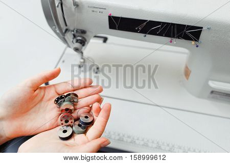 Female hands holding bobbins near sewing machine. Seamstress got several thread spools in palms, free space. Clothes making, professional tailor concept