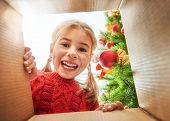 Merry Christmas and Happy Holidays! Cheerful cute child girl opening a Christmas present. Little kid poster