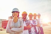business, building, teamwork and people concept - group of smiling builders and architect in hardhat poster