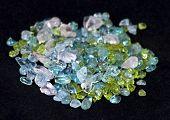 stock photo of peridot  - Chip beads of rose quartz peridot and aquamarine gemstones on black velvet background - JPG
