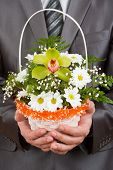 Happy Businessman With Basket Of Flowers