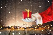 Santa Claus hand holding Christmas Gift box over wooden background. Proposing product. Advertisement poster