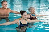 Smiling fitness class doing aqua aerobics in swimming pool. Smiling young woman with senior couple s poster