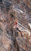 foto of sling bag  - A rock climber works his way up a rock face protected by a rope clipped into bolts - JPG