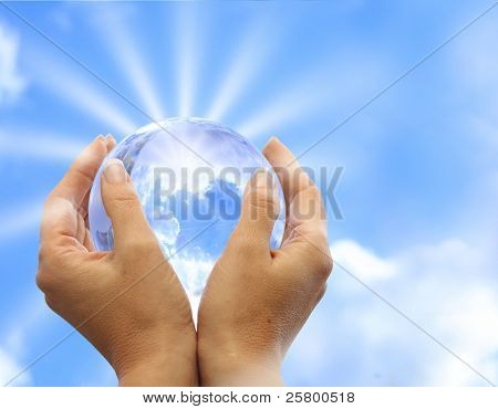 Globe in human hand against sun and blue sky. Environmental protection concept.