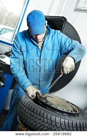 使轮胎管接头拧出一个轮子乳头的机械修理工