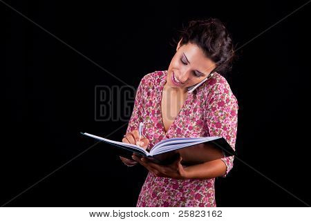 Beautiful And Happy Businesswoman Taking Notes On The Phone, Isolated On Black, Studio Shot