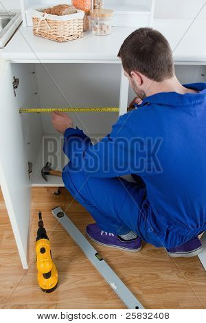 Portrait of a repair man measuring something in a kitchen