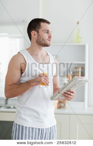 Portrait of a young man drinking orange juice while reading the news in his kitchen