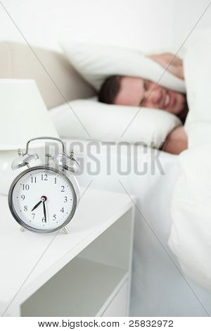 Portrait of a tired man covering his ears with a pillow while his alarm clock is ringing
