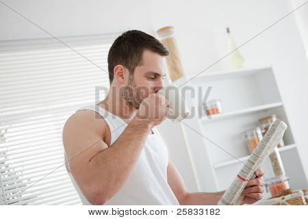 Young man drinking tea while reading the news in his kitchen