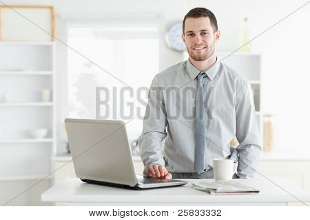 Businessman using a laptop while drinking tea in his kitchen