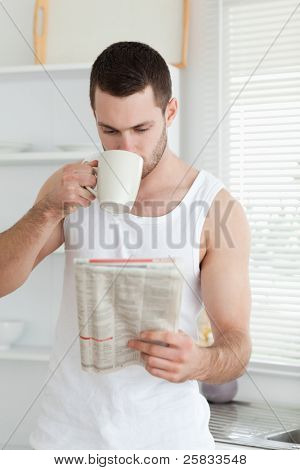 Portrait of a man drinking tea while reading the news in his kitchen