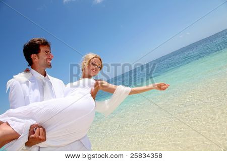 Groom holding bride in his arms by the sea