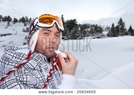 Portrait of a skier applying lip balm