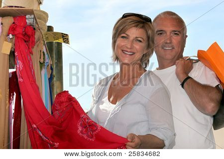Mature couple looking at sarongs in a holiday shop
