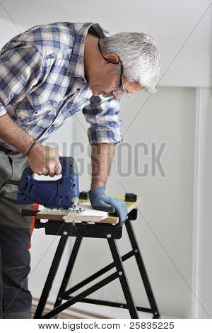 Senior carpenter sawing plank of wood