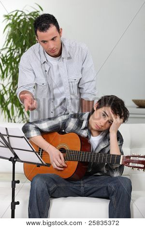 A father teaching his son how to play guitar.