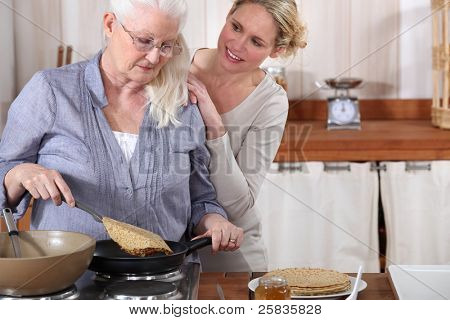 daughter helping her senior mother in the kitchen