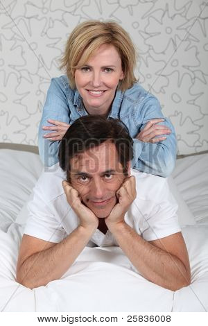 Married couple relaxing on bed