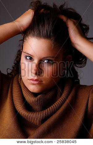 Beautiful Woman  With Hands Holding The Hair, Looking To Camera, Studio Shot