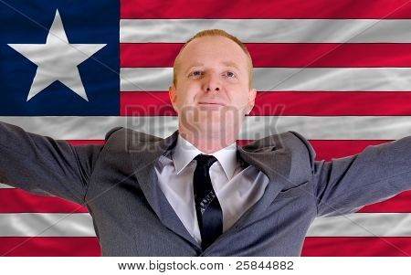 Happy Businessman Because Of Profitable Investment In Liberia Standing Near Flag