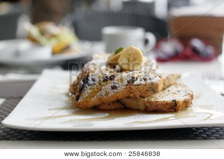 Cinnamon raisin french toast with maple syrup and french bananas