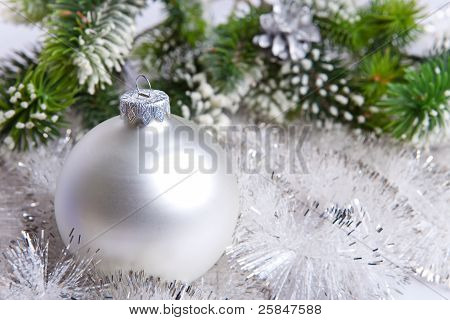 White nacreous glass New Year's ball and snow-covered branches of a Christmas tree