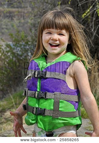 Cute 3 Year Old Caucasian Girl Smiling And Muddy In Life Vest