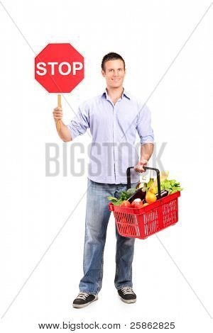 Full length portrait of a male holding a full shopping basket and a stop road sign isolated on white background