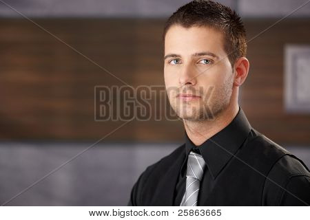 Portrait of bristly businessman in elegant office.?