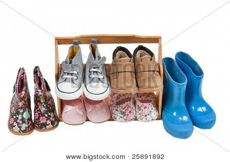 Girls shoos for all seasons arranged on a wooden shelf isolated on white