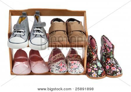 Children shoes for all seasons on a wooden shelf, isolated