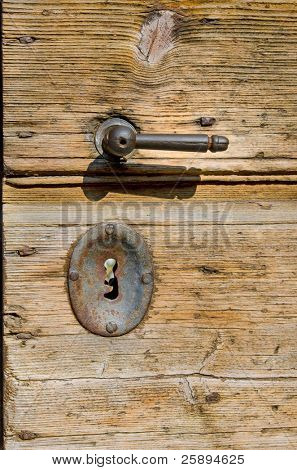 Old wooden door with rusty metal handle and key lock