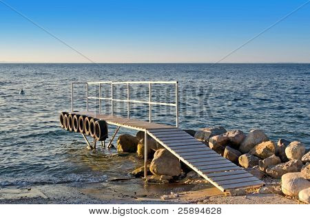 Wooden pier with tires on its side