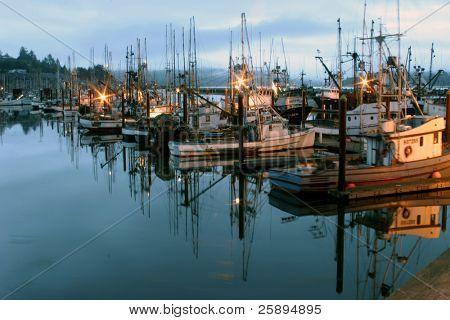 muelle de barcos de pesca durante la puesta del sol con reflejos en el agua a lo largo de la costa de oregon