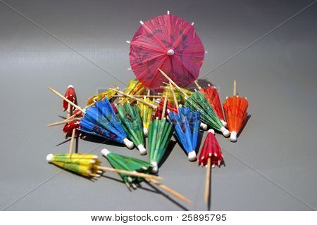 cocktail umbrellas of diffrent colors folded up with one open sit on a gray background