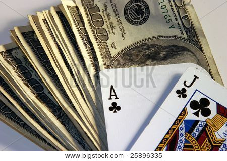 Black Jack hand laying on top of a pile of cash in $100.00 bills on a white background