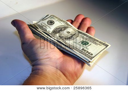 cold hard cash piled high and being held in the hand of a real human being against a white background