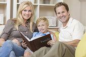 Постер, плакат: Привлекательный счастливый молодой семье матери отца и сына сидя на диване у себя дома глядя на p