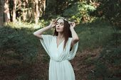 Tender Girl With Closed Eyes Posing In Floral Wreath In Forest poster