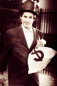 foto of olden days  - Selenium Photograph Of An Olden Day Male Banker Holding Dollar Sign Money Bags While On The Way To Deposit At The Bank In A Vintage Banking Investment Concept - JPG