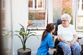Senior Woman Sitting In Motorized Wheelchair Talking With Nurse In Retirement Home poster