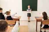 Little girl holding sign with crossed word Bullying in classroom poster